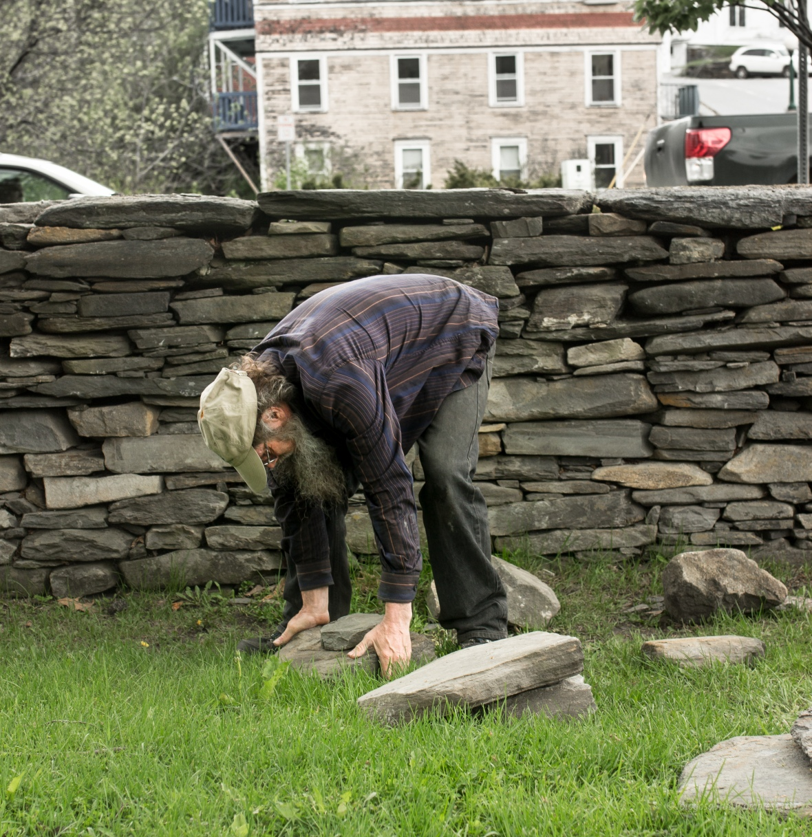 bending over lifting heavy stone
