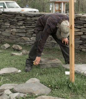 bending over measuring rock
