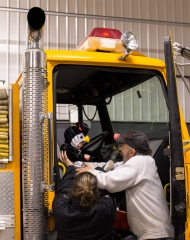 helping baby into firetruck